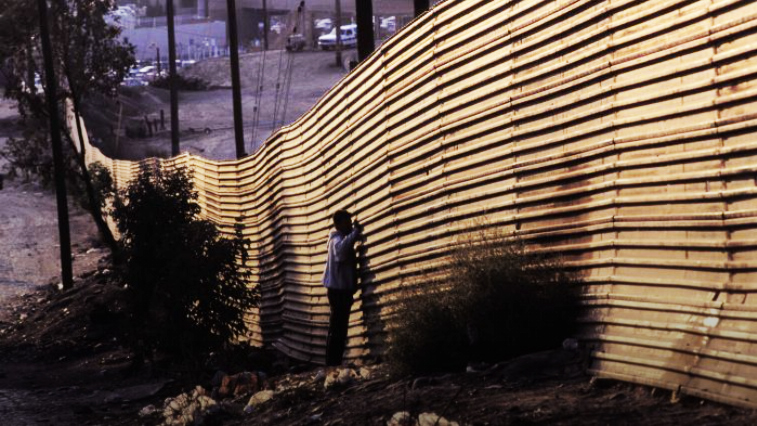 Image of person standing at a metal border wall